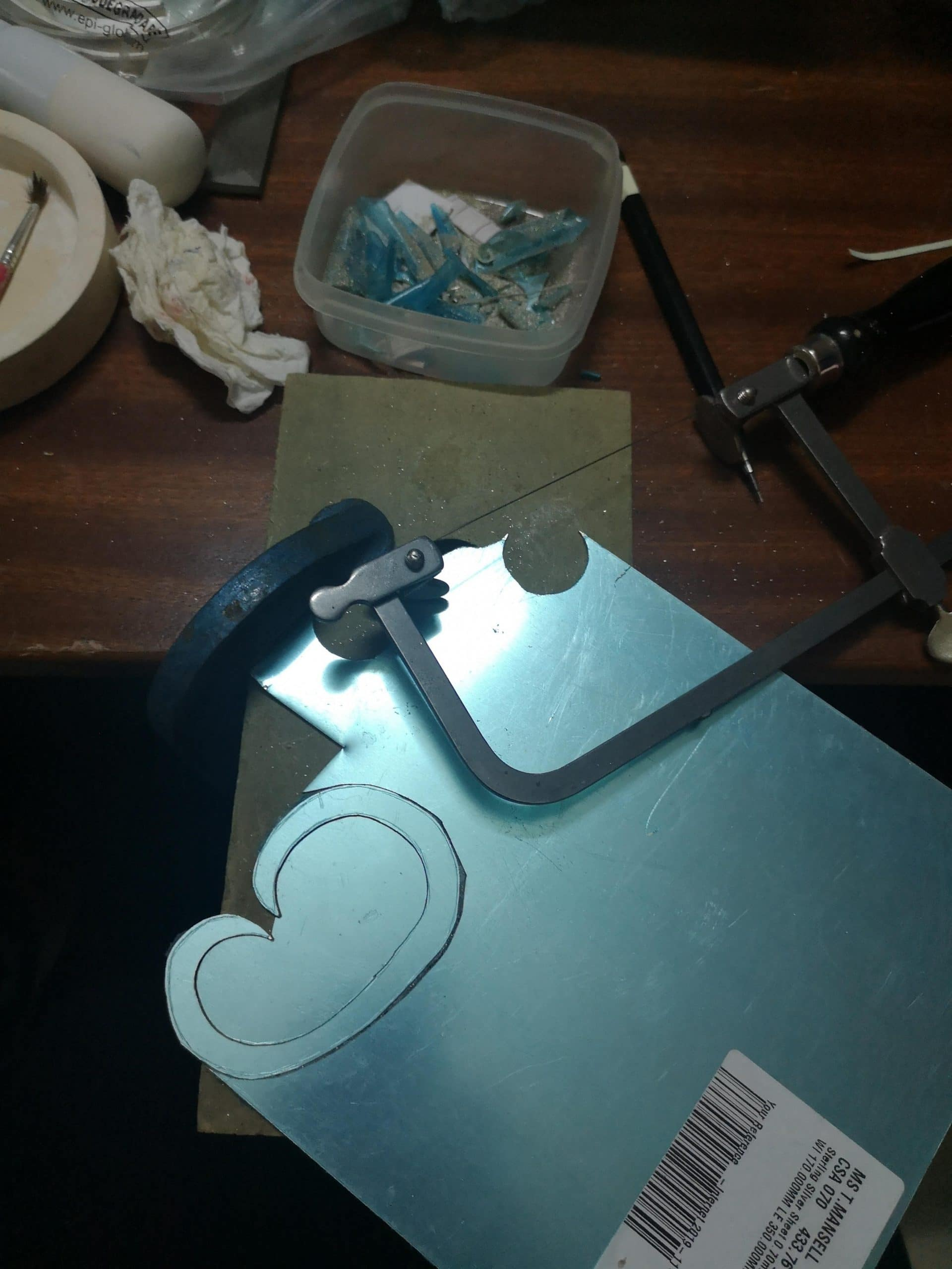 Cutting out the silver to make the Indian wedding brooch